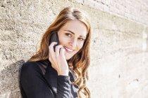 Ritratto di donna sorridente al telefono davanti al muro — Foto stock