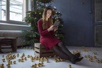 Femme souriante assise sur une boîte en bois devant un arbre de Noël décoré à l'aide d'une tablette — Photo de stock