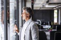 Зрелый бизнесмен в офисе смотрит в окно — стоковое фото