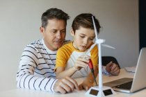 Father and son with laptop assembling wind turbine model — Stock Photo