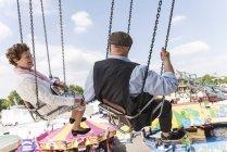 Casal sênior de mãos dadas no chairoplane na feira — Fotografia de Stock