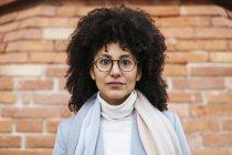 Retrato de mulher de raça mista grave contra parede de tijolo — Fotografia de Stock