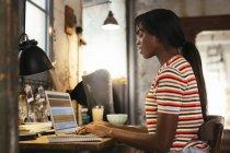 Jeune femme s'asseyant au bureau dans un grenier travaillant sur l'ordinateur portatif — Photo de stock