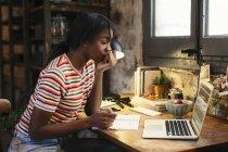 Пенсивна молода жінка, сидячи на столі в лофт дивиться на ноутбук — стокове фото