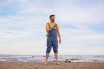 Uomo barbuto che beve bibite sulla spiaggia — Foto stock
