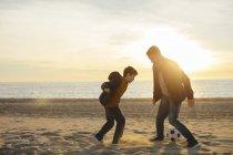 Pai e filho jogando futebol na praia ao pôr do sol — Fotografia de Stock