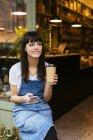Mulher de sorriso que senta-se na porta de entrada de uma loja que prende o telefone de pilha e o café takeaway — Fotografia de Stock
