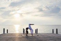 Junge Frau praktiziert Yoga auf einem Steg am Meer bei Sonnenuntergang, urdhva dhanurasana — Stockfoto