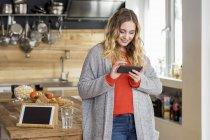 Portrait de jeune femme souriante utilisant un smartphone dans la cuisine — Photo de stock