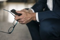 Cell phone and glasses in businessman's hand — Stock Photo
