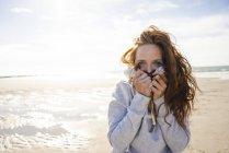 Рыжая женщина наслаждается свежим воздухом на пляже — стоковое фото