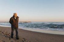 Seniorchef spaziert am Strand und blickt auf Meerwasser und Sonnenuntergangshimmel — Stockfoto