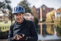 Портрет пожилого человека в велосипедном шлеме с помощью смартфона — стоковое фото