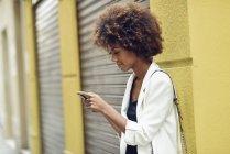 Sorrindo jovem mulher com cabelo encaracolado olhando para o telefone celular — Fotografia de Stock