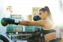 Sportive giovane donna boxe in città — Foto stock