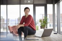 Портрет впевненої жінки, яка сидить на столі вдома з ноутбуком — стокове фото