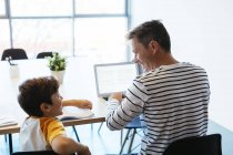 Smiling father and son sitting at table and using laptop — Stock Photo