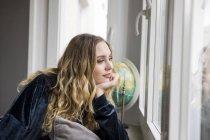 Ritratto di giovane donna che sogna ad occhi aperti guardando attraverso la finestra — Foto stock