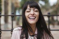 Retrato de rir jovem mulher com os olhos fechados ao ar livre — Fotografia de Stock