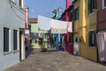 Itália, lagoa de Veneza, Burano, casas coloridas e lavanderia pendurada para secar — Fotografia de Stock