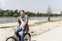 Зріла людина з велосипедом за допомогою смартфона на Рейні на березі Дніпра — стокове фото