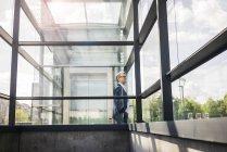 Empresário maduro em estrutura de vidro na cidade olhando ao redor — Fotografia de Stock