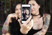 Mulher segurando celular com selfie de si mesma com seu parceiro lésbico — Fotografia de Stock