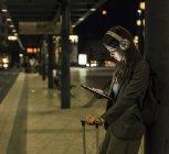 Jeune femme avec écouteurs et tablette en attente à la gare la nuit — Photo de stock