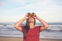 Женщина с биноклем на пляже — стоковое фото