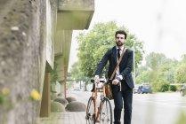 Homme d'affaires avec vélo marchant dans la rue — Photo de stock