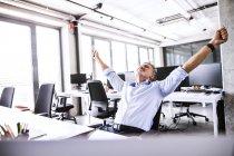 Glücklicher reifer Geschäftsmann sitzt mit erhobenen Armen am Schreibtisch im Büro — Stockfoto