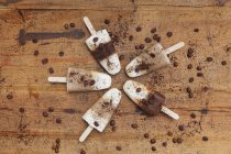 Homemade Espresso Macchiato and Latte Macchiato ice lollies with coffee beans on wooden background — Foto stock