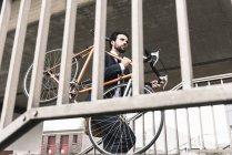 Homme d'affaires portant un vélo à la gare — Photo de stock