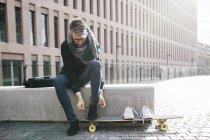 Фрилансер с лонгбордом, сидящий на скамейке и привязывающий ботинки — стоковое фото