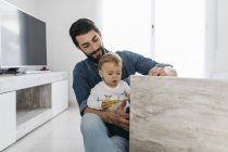 Father and daughter assembling a wooden table at home — Stock Photo