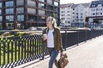 Jeune femme marchant sur le pont, buvant du café, écoutant de la musique avec écouteurs — Photo de stock