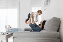Father playing with his daughter at home — Stock Photo