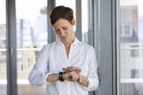 Деловая женщина у окна в офисе проверяет время — стоковое фото