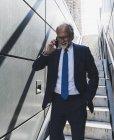 Sorrindo empresário maduro em escadaria na cidade no telefone celular — Fotografia de Stock