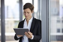 Businesswoman using tablet at the window in office — Stock Photo
