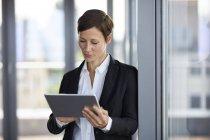 Empresária usando tablet na janela do escritório — Fotografia de Stock