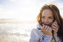 Donna dai capelli rossi godendo di aria fresca in spiaggia — Foto stock