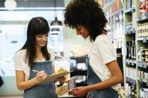 Deux femmes souriantes dans un magasin avec presse-papiers — Photo de stock
