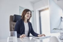 Улыбающаяся молодая деловая женщина, работающая за столом в офисе — стоковое фото