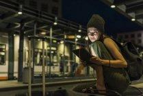 Портрет молодої жінки з навушниками і планшетом очікування на вокзалі вночі — Stock Photo