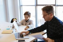 Businessman using laptop at desk in office with son sitting next to him — Stock Photo