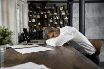 Mature businessman sleeping on desk in loft — Stock Photo