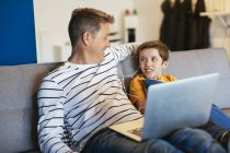 Отец и сын с наушниками и ноутбуком отдыхают на диване дома — стоковое фото