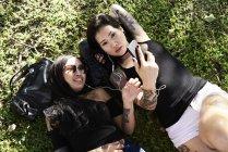 Tatuato amiche di sesso femminile ascoltare musica sdraiato sull'erba — Foto stock