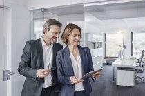 Улыбающийся бизнесмен и деловая женщина используют планшет в офисе вместе — стоковое фото
